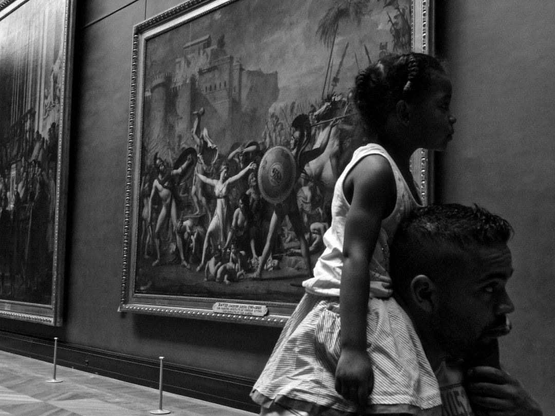 """Un père et sa fille sur ses épaules au Musée du Louvre à Paris, dépassant le tableau de Jacques Louis David """"L'enlèvement des Sabines"""""""
