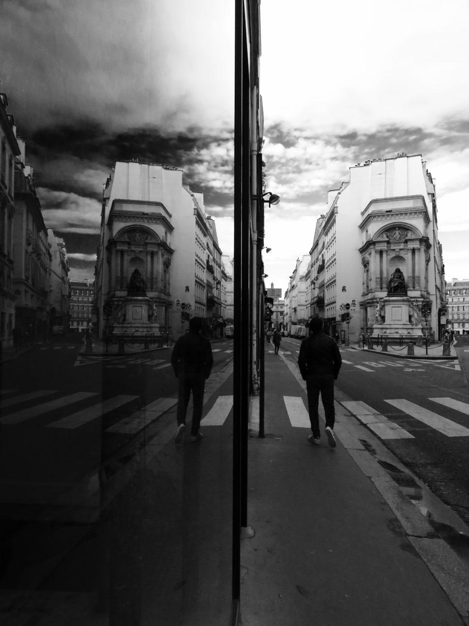 Photo en noir et blanc de la fontaine Molière, rue de Richelieu, à Paris, se reflétant dans une vitre
