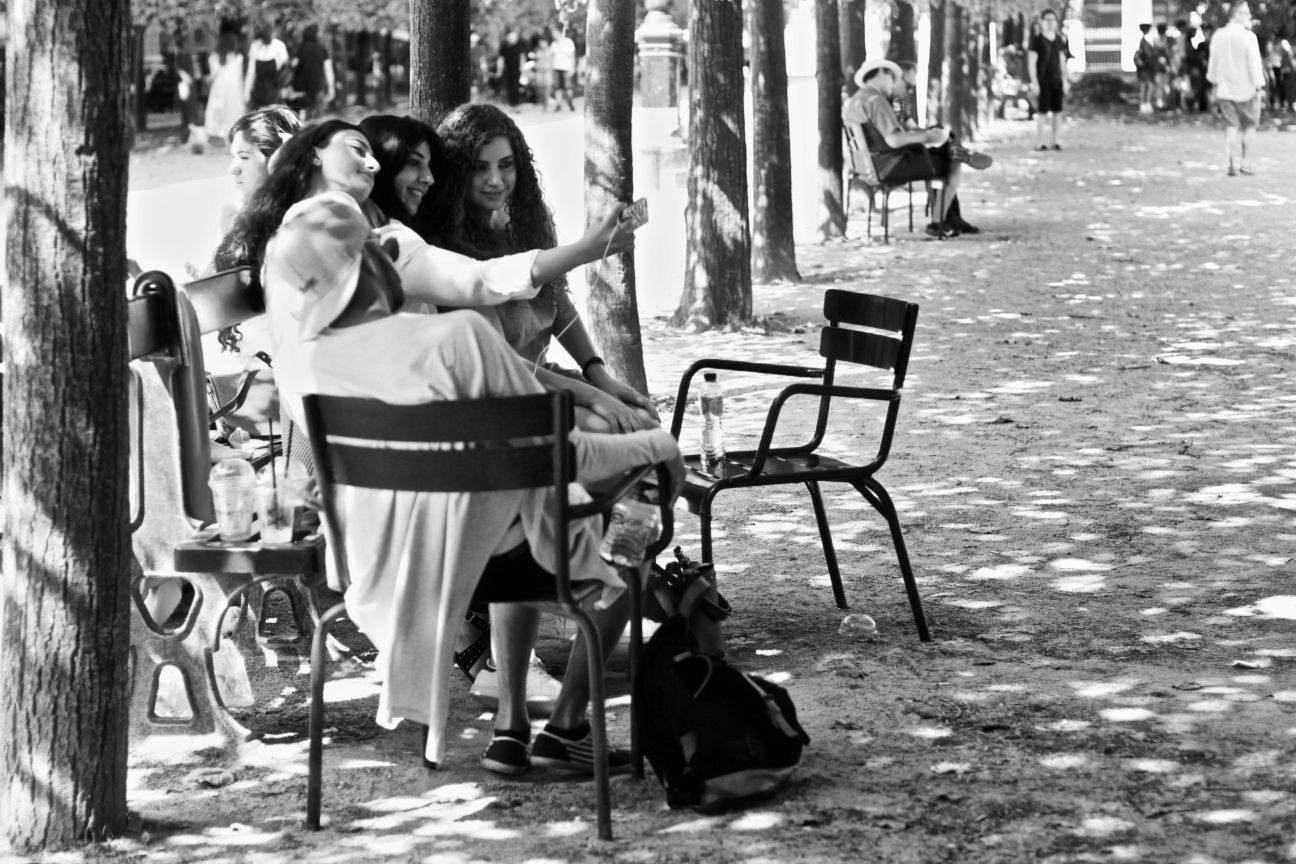 Photo en noir et blanc de jeunes filles assises sur un banc des jardins du Palais Royal, à Paris, en train de se prendre en photo avec le téléphone de l'une d'elles