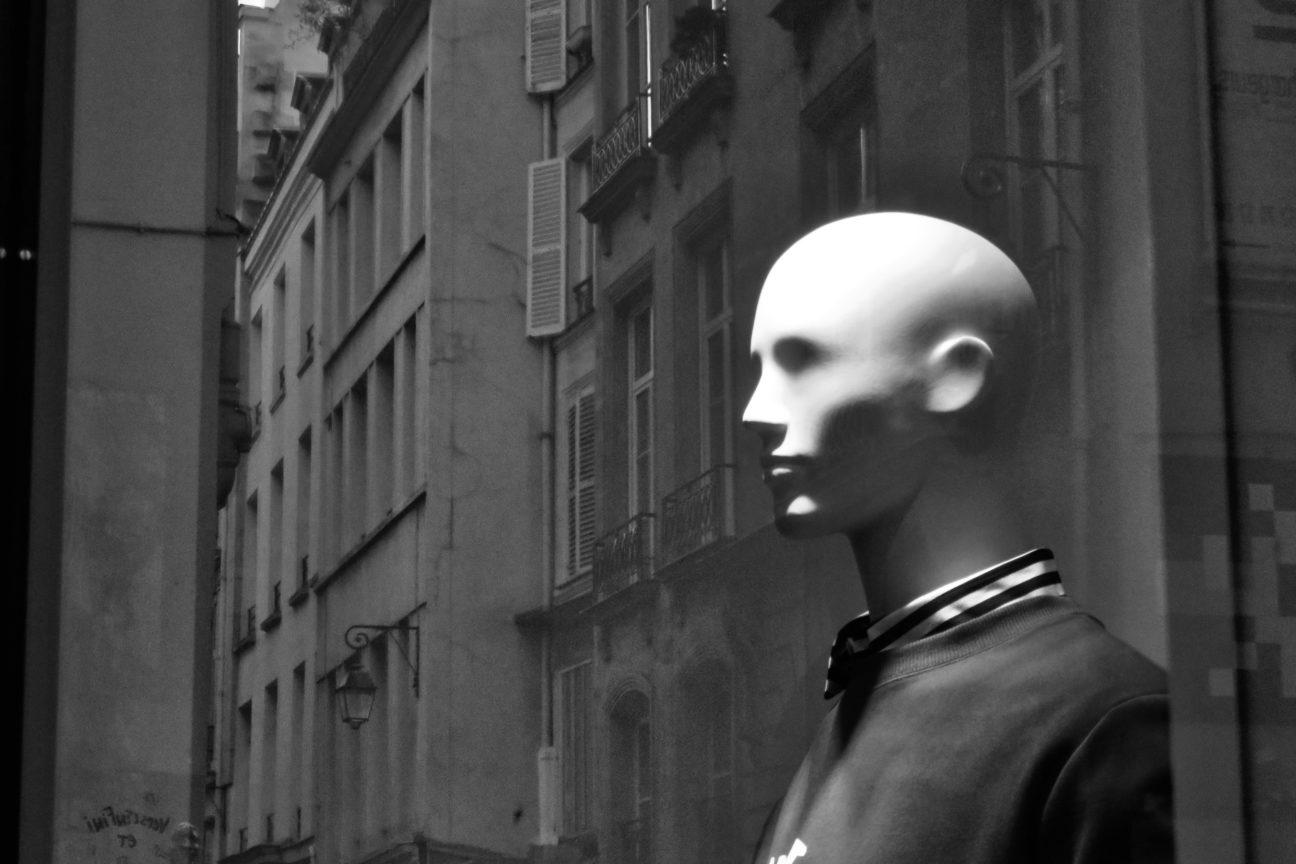 Tête de mannequin dans une vitrine, photo en noir et blanc et se surimprimant sur ce visage de celluloïd les façades des immeubles de la rue d'en face, Rue de Rivoli, Paris - Automne 2017