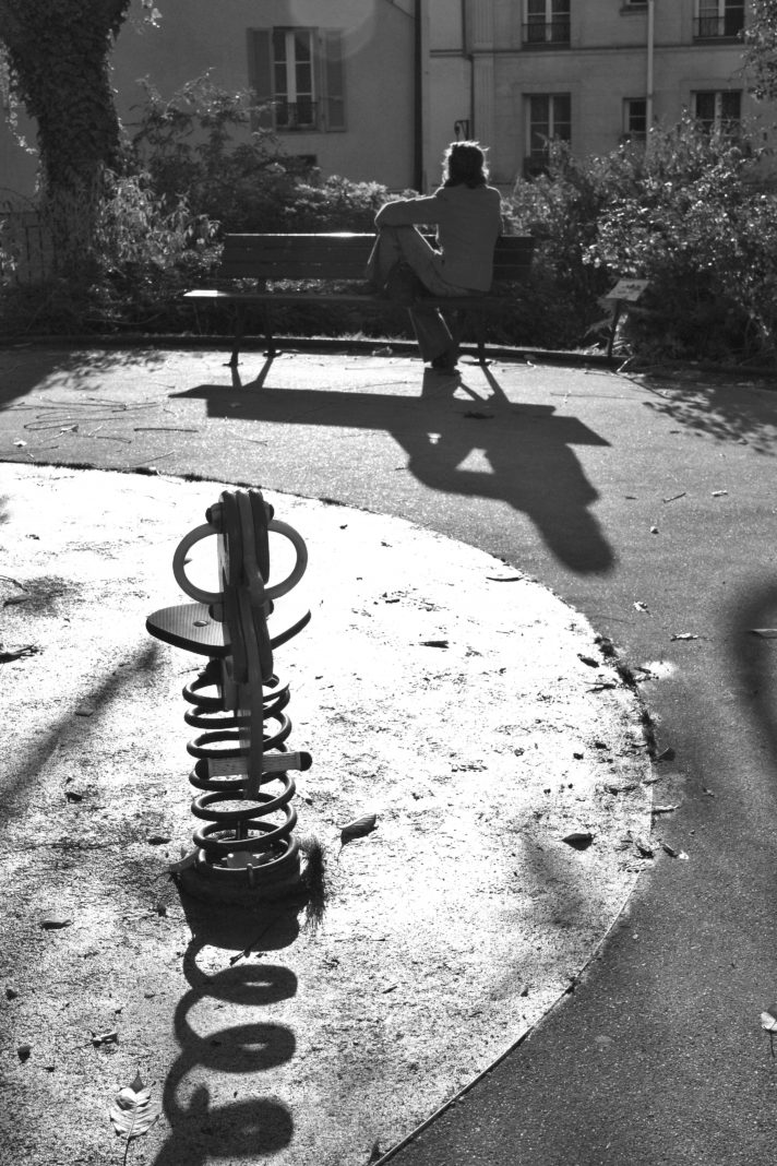 Photo en noir et blanc d'un jardin d'enfant, avec un jeu au premier plan et au fond la silhouette d'une femme de dos, assise sur un banc