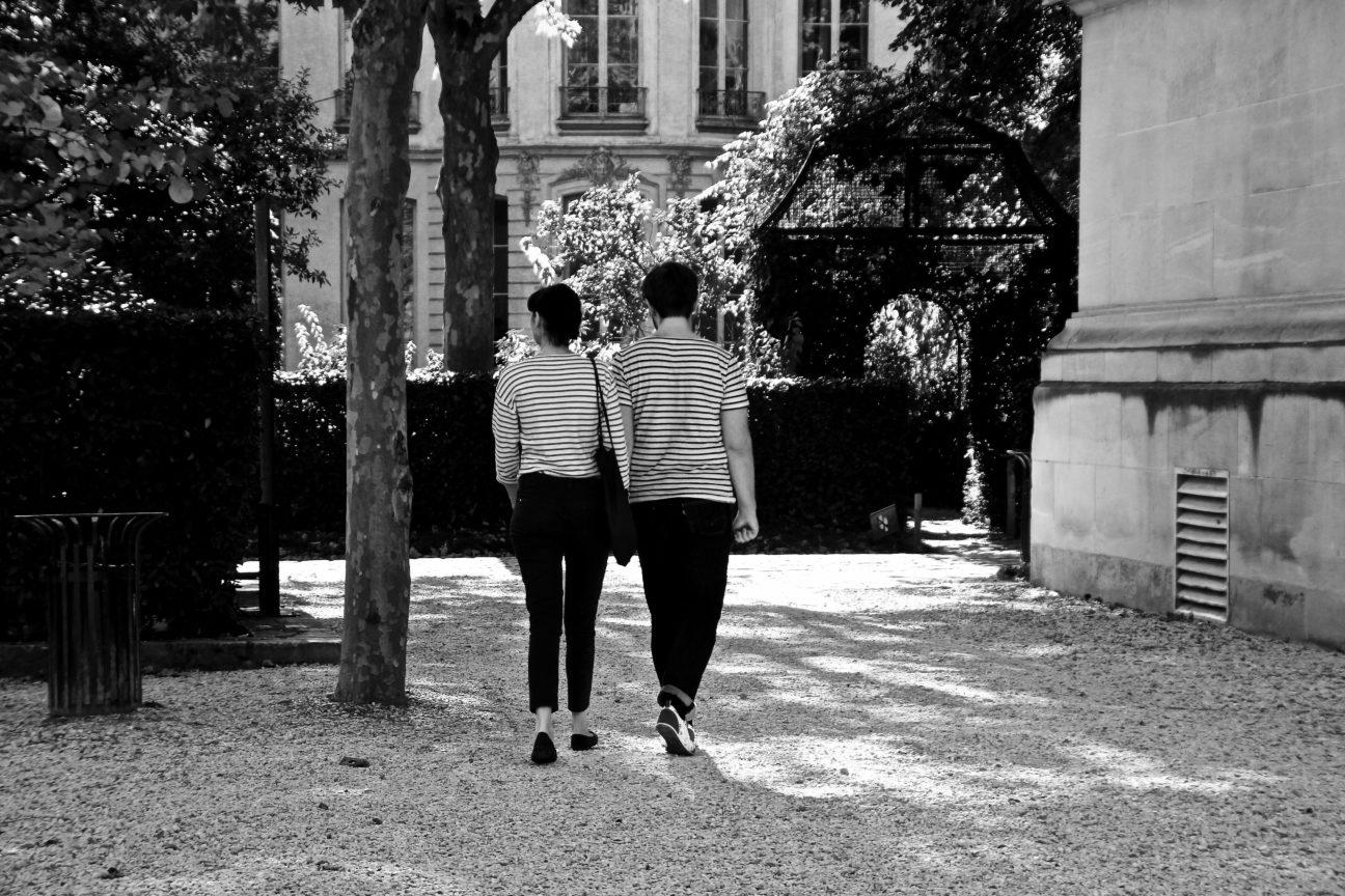 Photo en noir et blanc d'un couple d'amoureux tous deux portant un haut rayé, main dans la main dans le Jardin des Archives Nationales, à Paris