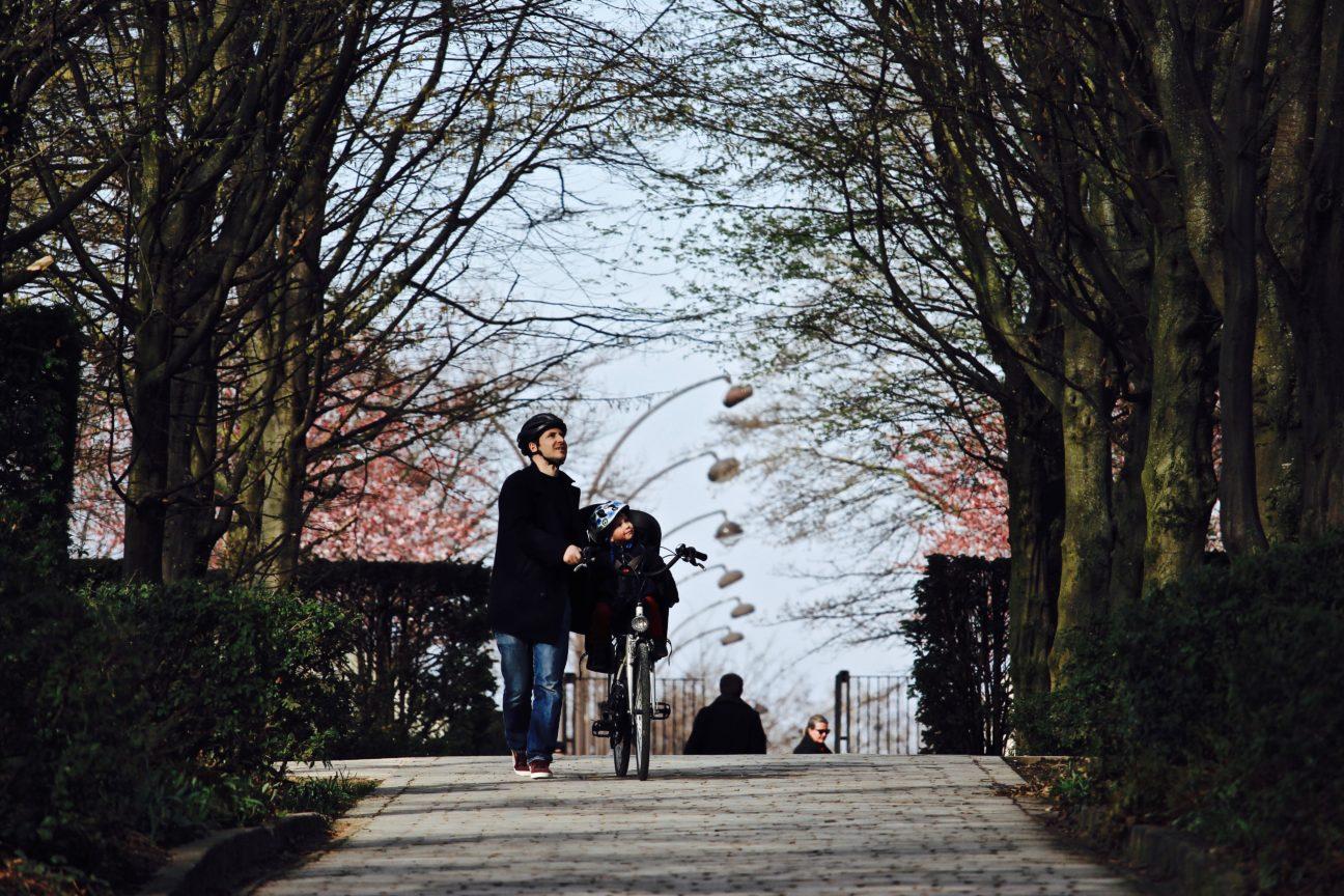 Photo en couleurs d'un père et son petit garçon, lequel est juché sur un vélo poussé par le papa, qui traversent une allée du Parc André Citroën, à Paris ; photo prise en mars 2018