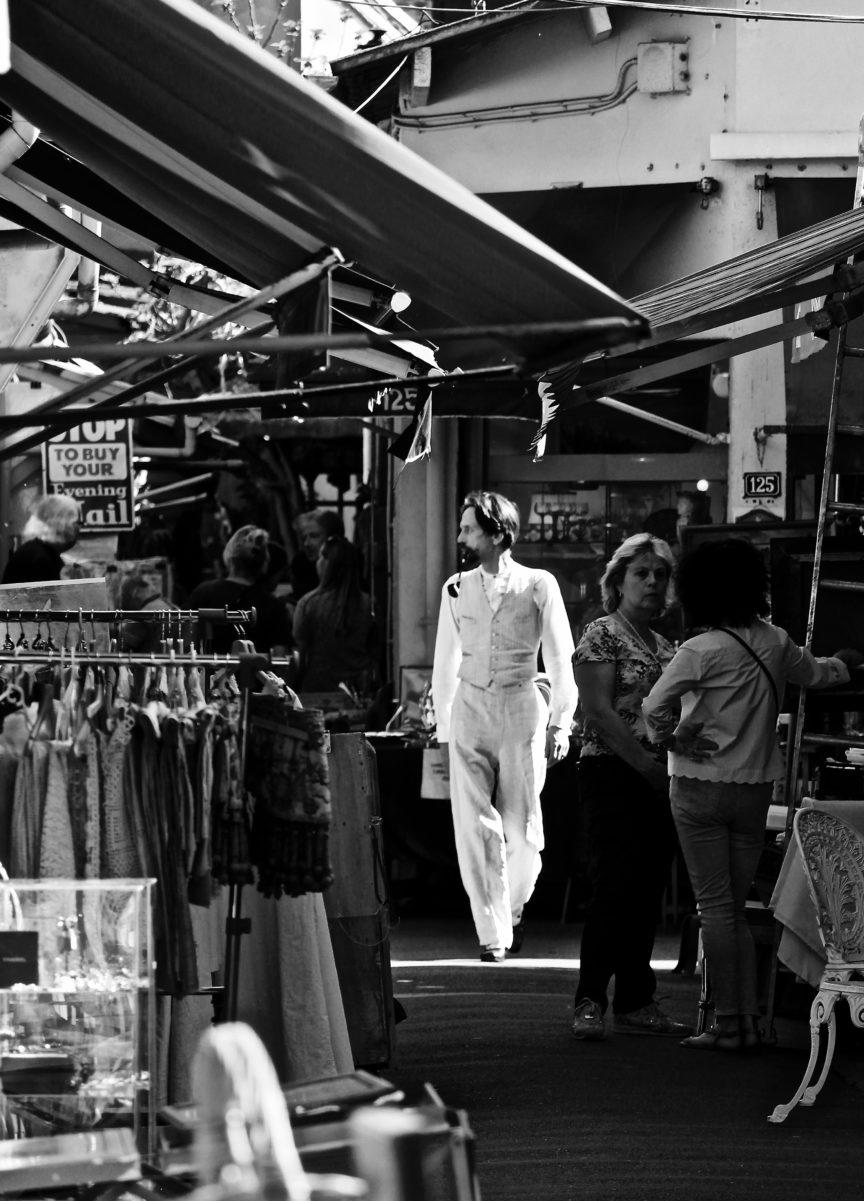 Photo en noir et blanc d'un homme en blanc très élégant, vêtu comme au 19e siècle, au Marché aux Puces de Saint-Ouen ; l'homme s'avance sans se rendre compte qu'il est pris en photo, du soleil au-dessus de lui