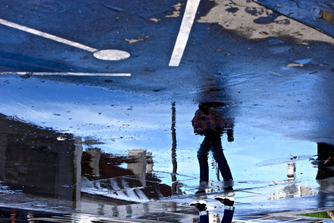 Photo en couleurs d'une silhouette de femme en réflection dans une flaque d'eau Place de la Bastille, en février 2018
