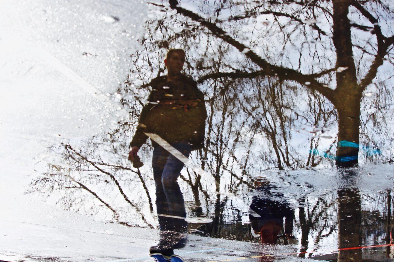 Photo en couleurs prise Place de la bastille à Paris en février 2018, au moment du dégel, représentant une silhouette d'homme capturée dans une flaque d'eau, prise dans le reflet de branches d'arbres