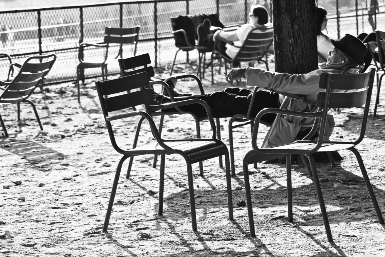 Photo en noir et blanc d'un homme les yeux fermés étendu sur une chaise du Jardin des Tuileries, en automne 2018, les pieds suspendus sur une autre chaise